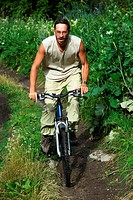 Mountain biker on old rural road in forest