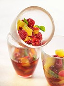 Summer fruit with orange juice and rose petals