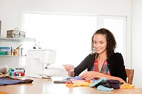 Attractive young woman sewing garments
