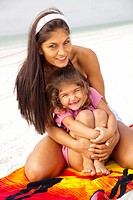 Mother hugging pre_teen daughter on beach towel