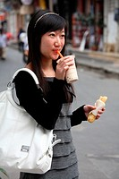 A girl with Er kuai rice cake and soybean milk the traditional Kunming style breakfast on the street Kunming  China