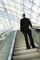 rear view of businessman on escalator