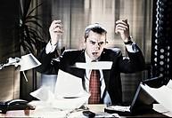 manager arrabbiato in ufficio, fogli in aria