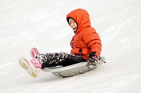 Girl sliding down a city park hill in the winter age 7  St Paul Minnesota MN USA