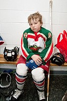 Boy age 8 in locker room wearing hockey uniform tired after a game  St Paul Minnesota MN USA