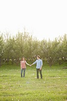USA, Utah, Provo, Young couple walking through orchard