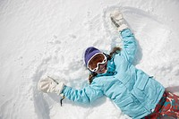 Girl 10_11 in ski gear doing snow angel