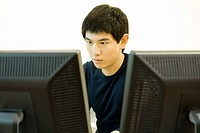Young man working on computer with two monitors