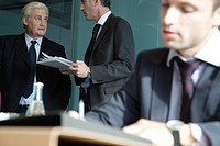 Executive in discussion, young businessman working in foreground (thumbnail)