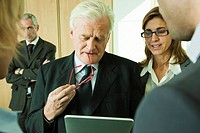 Mature executive examining information on digital tablet with colleagues