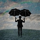 Silhouette of man holding two umbrellas in rain