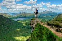 Hiker looking out across Loch Lomond and Trossachs National Park from Ben Vane.