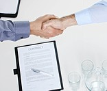 Handshake over contract on table