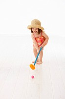 Little girl playing golf indoor