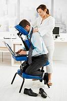 Masseur doing neck massage in office