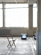 Television and wooden chair in empty warehouse