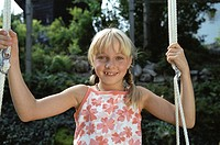 Blonde Girl sitting on Swing _ Garden _ Summer