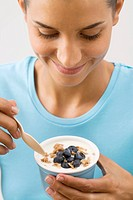 Young woman eating muesli with blueberries, Munich, Bavaria, Germany