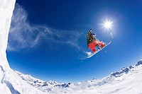 A snowboarder flying over snow covered peaks.