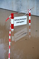 Germany, Wuerzburg, Warning sign in flood water