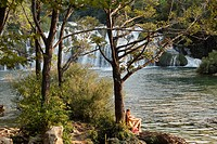 Croatia, Dalmatia, Couple siiting by krka waterfalls at krka national park