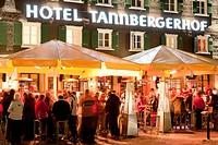 Austria, Vorarlberg, Lech am Arlberg, View of people at Tannbergerhof hotel and pub in winter