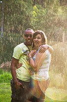 A happy, young, african-american couple playing in the rain