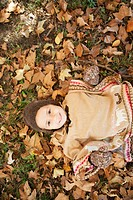 Mixed race girl laying in autumn leaves