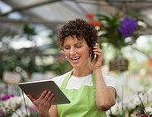 Hispanic woman using digital tablet and cell phone in plant nursery