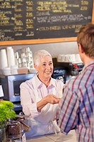 Caucasian woman serving customer coffee in cafe