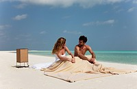 Couple sitting in bed on beach