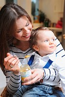 Woman feeding toddler son baby food