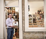 Wine merchant with case of wine in shop