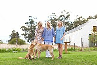 Mother and daughters with dogs in garden