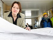 Businesswoman examining blueprints