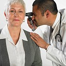 Doctor examining older woman's ears