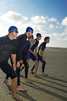 Swimmers standing in row on beach