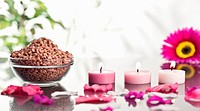 Lighted pink candles with petals and a bowl of gravel with a pink gerbera in the background