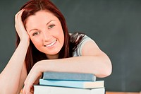 Close up of a smiling young student with her forearm on her books in a classroom