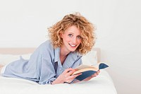 Good looking blonde woman reading a book while lying on her bed in her appartment