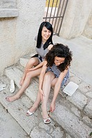 Two attractive young women are sitting after a night out, sore feet