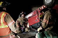 Three Firefighters Near Flipped Car