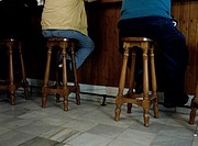 Men Sitting on Stools at Bar