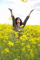 A happy young caucasian woman in a field of canola