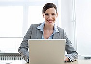 Young business woman with laptop, smiling