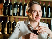 Young woman drinking red wine in cafe
