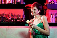 Happy young woman sitting at cocktail bar (thumbnail)