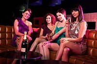 Four young women enjoying champagne in nightclub