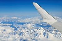 Wings of flying airplane over French Alps