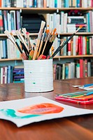Children's paintbrushes and paintings on table